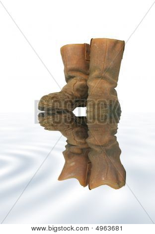 Dirty brown leather builders boots with reflection in grey water over white background. poster