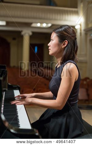 Woman pianist sits at the piano in empty concert hall
