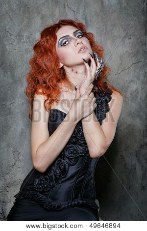 Red-haired vampire girl with red lips posing in urban twilight poster