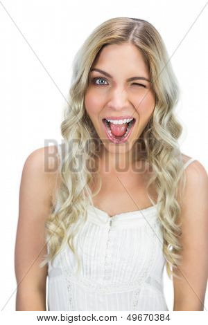 Cheerful blue eyed model on white background winking at camera