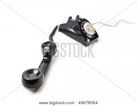 Old 60s - 70s style black telephone with rotary dial. Isolated on white. Hand set off the hook and unattended.