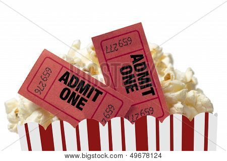 Close up shot of red movie tickets in a tub of delicious popcorn and shot on white background. poster