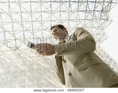 Low angle view of happy businessman reading SMS on mobile phone under ceiling