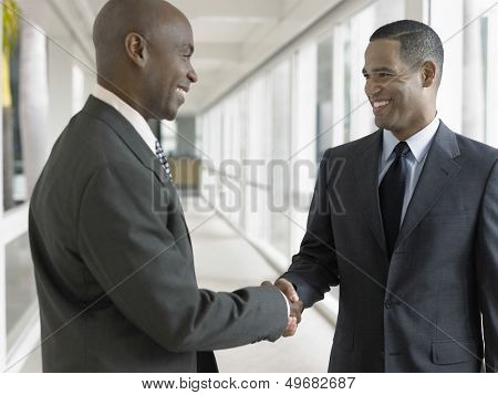 Happy African American businessmen shaking hands while standing in office corridor