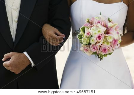 Midsection of bride standing arm in arm with father