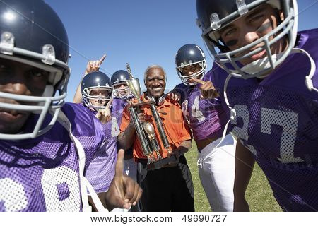 Portrait of happy football team and coach with trophy celebrating victory on field