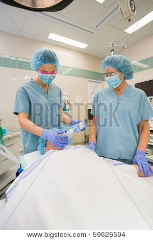 Anesthesiologist sedating a patient in surgical theater