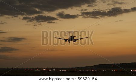 Plane landing in a sunset