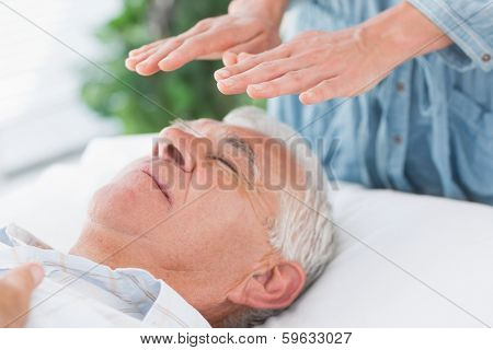 Massage therapist performing Reiki over senior man at health spa poster