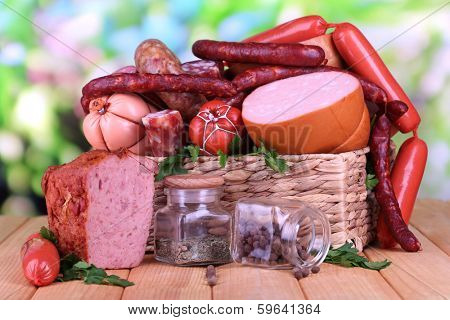 Lot of different sausages in basket on wooden table on natural background poster