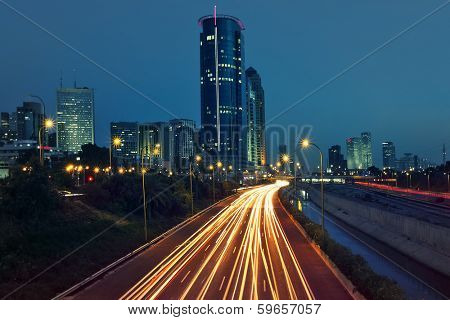 View of Ayalon highway, light traces and modern buildings in evening at downtown of Tel Aviv, Israel.