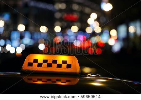 Illuminated taxi cab sign on a city street