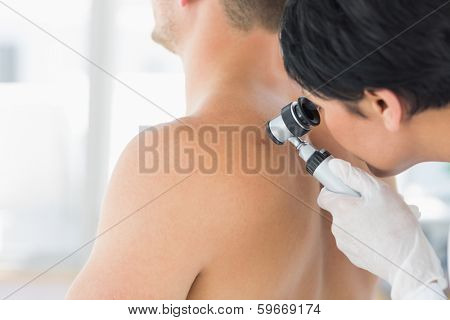 Female doctor examining mole on back of man in clinic poster