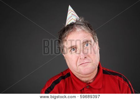 Sad man wearing a party hat