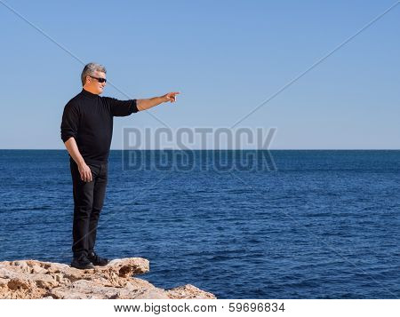 Mature Middle-age Man Standing On A Rock Pointing