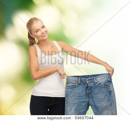 fitness, diet and good shape concept - sporty woman showing big pants poster