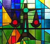 Modern stained glass window depicting the cross balancing the scales of justice as symbol of social justice poster