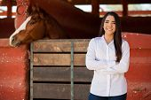 Beautiful business owner posing in front of her ranch and some horse stables and smiling poster