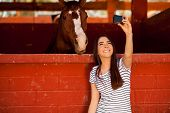 Cute young brunette taking a selfie with his horse in the stables poster