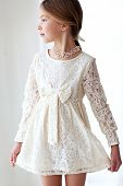Fashion 7 years old model dressed in ivory lace dress pastel tone poster