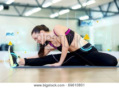 fitness, sport, training, technology and lifestyle concept - smiling young woman stretching on mat in gym