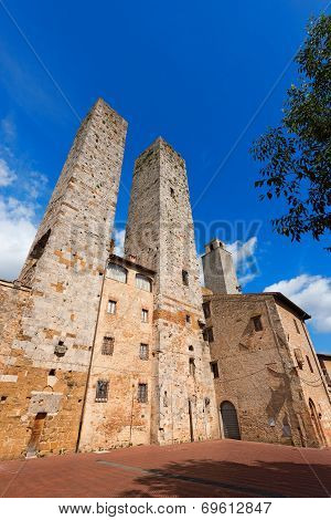 Three towers and houses in Piazza delle Erbe San Gimignano medieval town (UNESCO heritage) Siena Tuscany Italy poster