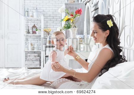 Mother Playing With A Year-old Daughter On The Bed
