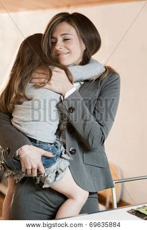 Mother embracing her little girl before leaving to work/or just back from work