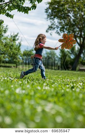 Little girl playing outdoors, running with pinwheel