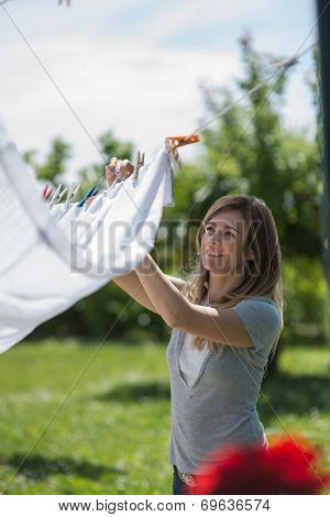 Young woman hanging up laundry