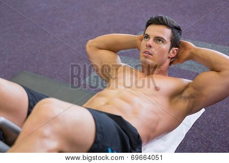 High angle view of muscular man doing abdominal crunches in gym