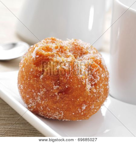 closeup of a bunuelo de viento, a typical pastry of Spain, eaten in Lent, served on a plate and a cup of coffee