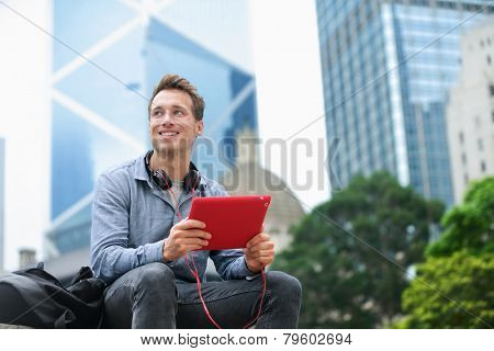 Urban man using tablet computer sitting in Hong Kong outside using app on 4g wireless device wearing headphones. Casual young urban professional male in his late 20s. Hong Kong Central.