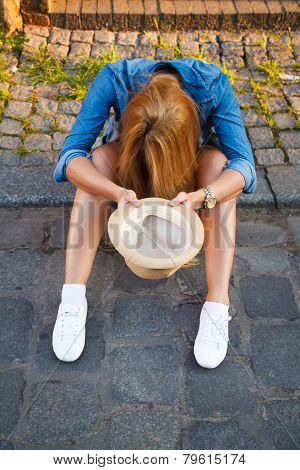 Young woman begging with a hat