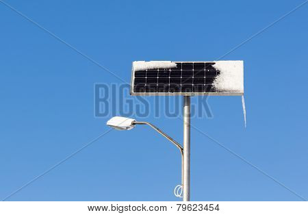 Solar Power Street Light With Snow And Ice On Blue Sky Background