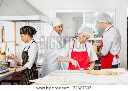 Male and female chefs preparing pasta in commercial kitchen