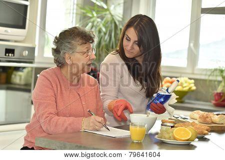 Homecare helping elderly woman doing crossword