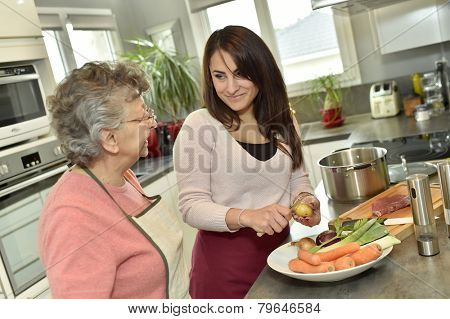 Homecare cooking dinner for elderly woman