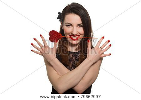 Erotic Looking Woman With Red Lipstick Holding Valentine Heart In Her Mouth Teeth. Showing Red Nails