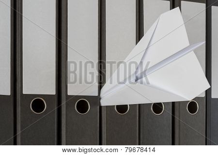 Paper Plane Stuck Between Folders