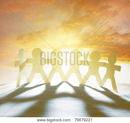 Team of six paperchain people holding hands in front of bright sky