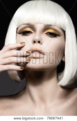Beautiful girl in a white wig, with gold makeup and nails. Celebratory image. Beauty face. Picture t