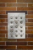Retro Filter Photo Of Grungy Old Apartment Intercom Or Buzzer Against Brick Wall poster