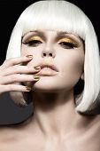 Beautiful girl in a white wig, with gold makeup and nails. Celebratory image. Beauty face. Picture taken in the studio. poster