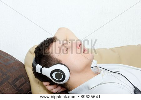 Young Man Daydreaming Listening To Music Over Headset