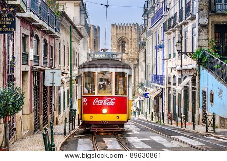 LISBON, PORTUGAL - SEPTEMBER 12, 2014: A tram passes the Lisbon Cathedral. The historic trams are a popular attraction.