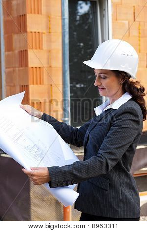 Architect With Blueprint On Site Prior To Shell The House.