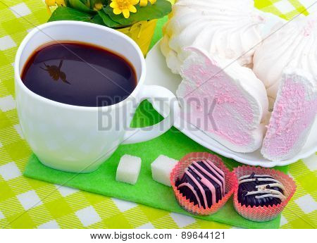 Cup Of Coffee With Marshmallows And Chocolate Candies On A Green Napkin