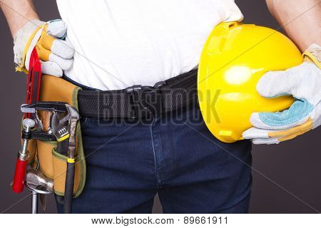 Worker with toolbelt and helmet against dark background