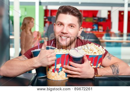 Young man buying popcorn and drinks